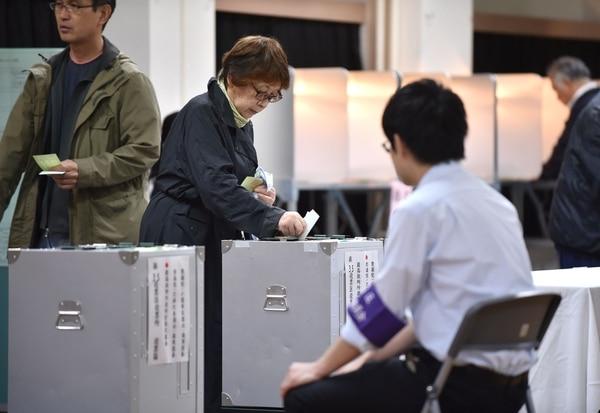 Una mujer da su voto en las elecciones generales de Japón, en una mesa electoral en Tokio, Japón.