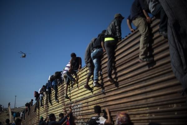 Un grupo de migrantes escaló una valla cerca del cruce fronterizo de Chaparral, entre México y Estados Unidos, este domingo 25 de noviembre del 2018.