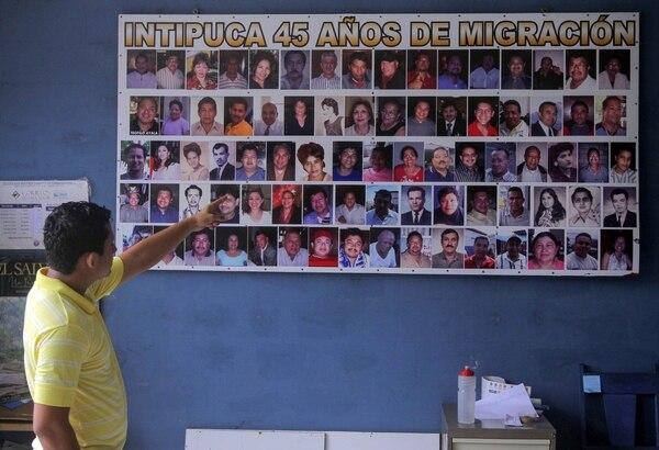 Un hombre apunta a un cartel con fotos de los emigrantes, en Intipuca 179 kilómetros al sureste de San Salvador.