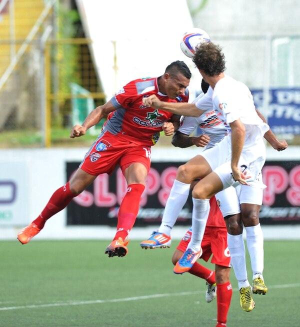 El delantero Cristhian Lagos intenta un remate de cabeza ante la marca de Darío Delgado (al fondo) y Raymond Fernández, de Puntarenas. | MANUEL VEGA