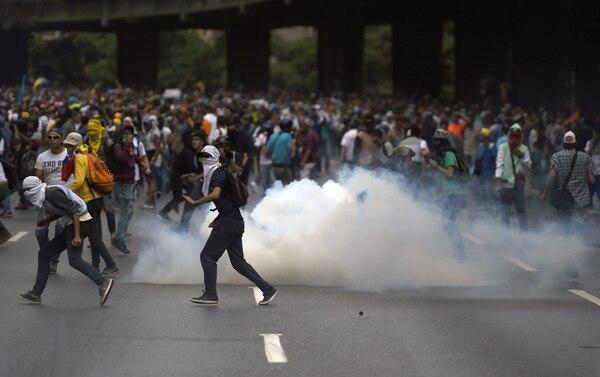 Opositores venezolanos participan este jueves en una manifestación contra el gobierno del presidente Nicolás Maduro en Caracas.