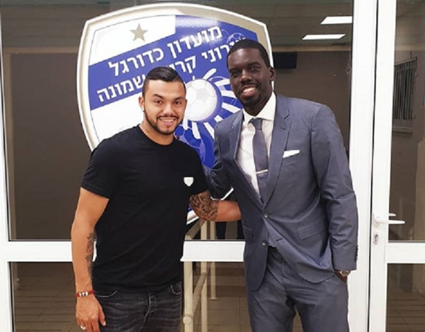 John Jairo Ruiz junto a su representante Joaquim Batica en la firma de su contrato por dos años en Israel. Fotografía: Instagram de Joaquim Batica.