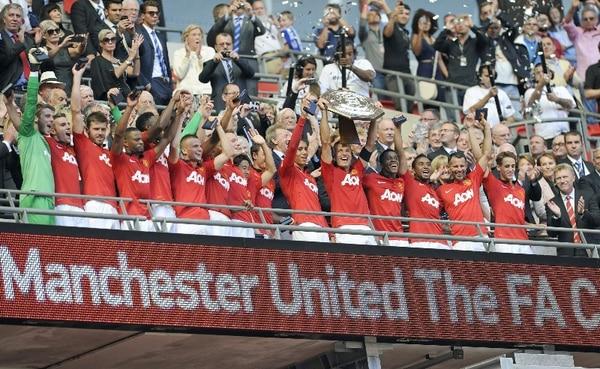 El capitán Nemanja Vidic alza la copa que otorga al Manchester United la Community Shield. | EFE