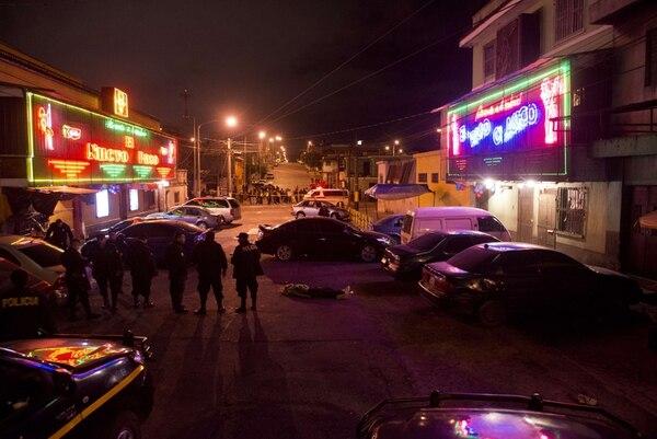 Policías custodian la escena de un homicidio en Ciudad de Guatemala, el 30 de noviembre. Presuntos miembros de la mara 18 atacaron frente al club nocturno El Paso Clásico, mataron a tres personas e hirieron a varias. | AFP