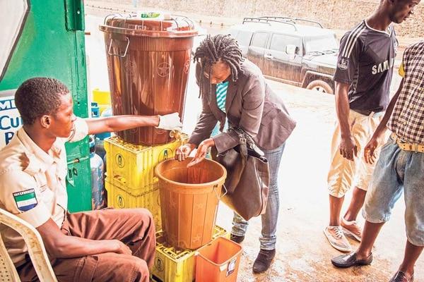 Esta mujer se lava las manos para que le permitan entrar a un edificio en la capital sierraleonesa, Freetown. La medida es parte de una campaña de prevención contra el ébola.