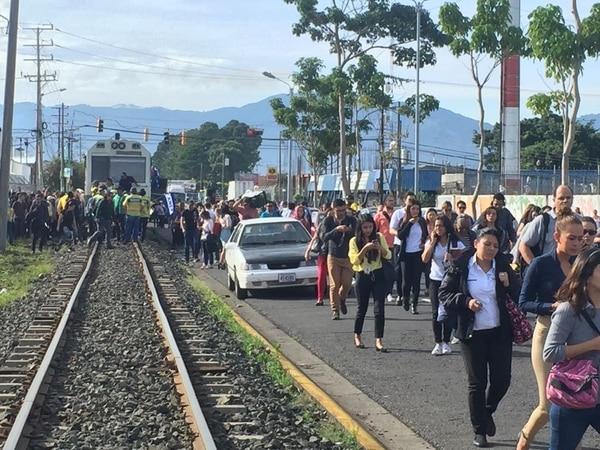 Empleados de la Municipalidad de San José bloquean la línea férrea detrás de la sede del ayuntamiento. Pasajeros tuvieron que bajar de los vagones. Foto Rafael Pacheco.