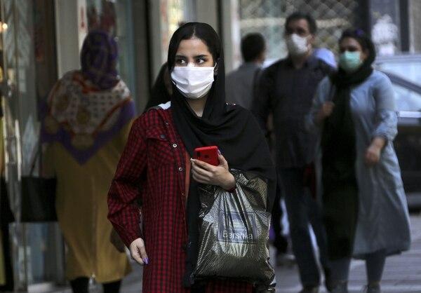 Una mujer, vestida con una mascarilla como precaución contra la pandemia del coronavirus, camina frente a las tiendas a lo largo de una calle en la capital de Irán, Teherán, el 27 de setiembre del 2020. Foto: AFP