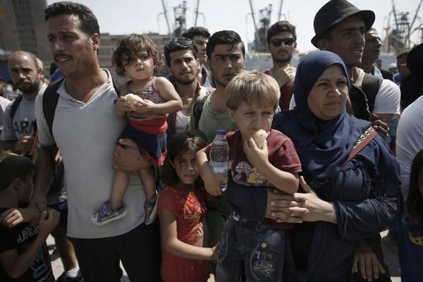 Refugiados esperan un autobús, luego de desembarcar del ferry en el puerto de El Pireo, en Atenas. La mayoría son Sirios que vienen desde Turquía huyendo de la situación de su país.