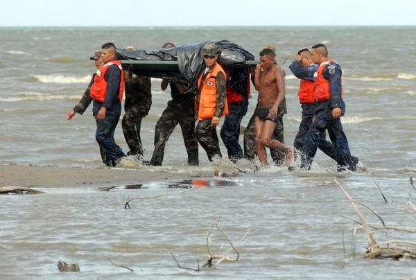 Personal de rescate traslada el cadáver de una de las víctimas del accidente aéreo en el lago de Managua.