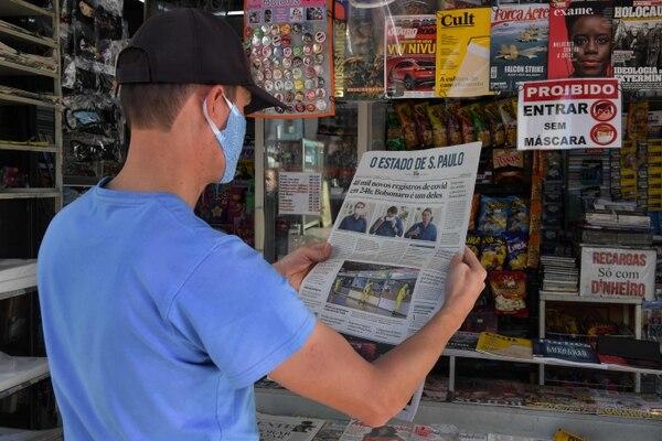 Un hombre observa la portada de un periódico con la noticia del presidente brasileño Jair Bolsonaro como un caso confirmado del nuevo coronavirus, en un puesto de periódicos en Río de Janeiro, Brasil, el 8 de julio del 2020. Foto: AFP