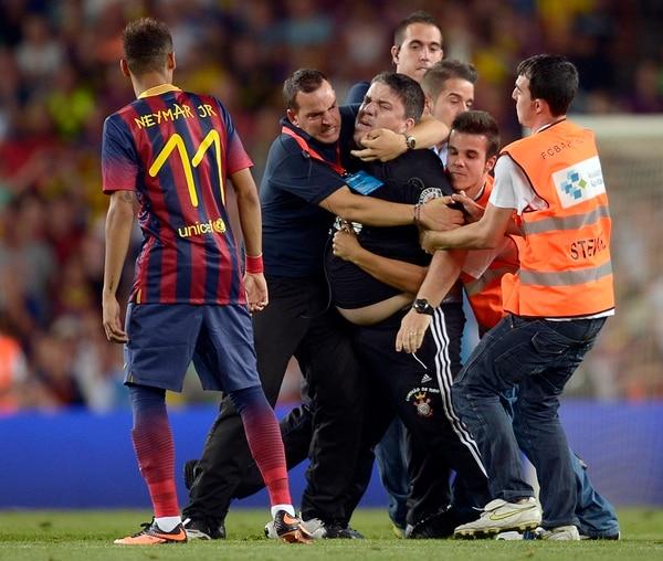 La seguridad del Camp Nou detuvo a un seguidor, vestido con los colores del Corinthians, que ingresó al campo para saludar a Neymar (11). | AP