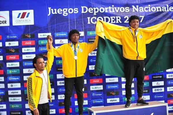 Kervin Arboine (izquierda) tuvo el honor de premiar a sus hermanos Keyshewen y Kenney (derecha) en la final del salto largo de los Juegos Nacionales, quienes ganaron plata y oro respectivamente, en la categoría Juvenil B.