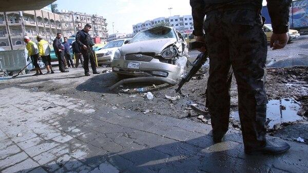 Policías custodian el área donde estalló ayer uno de los nueve coches bomba en la ciudad de Bagdad. | AFP