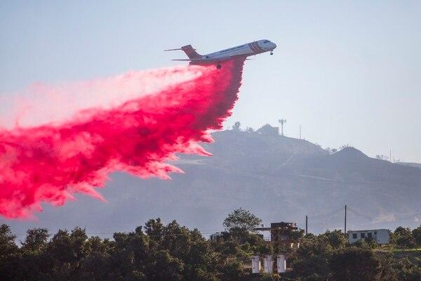 Un avión cisterna arrojó una sustancia retardante del fuego como parte del combate al incendio María en el condado de Ventura, California, este viernes 1.° de noviembre del 2019.