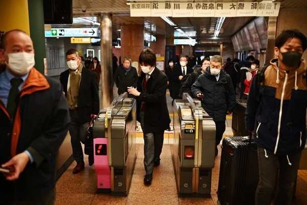 People wait for the train in Tokyo's Ginza area on February 17, 2020. - Japan said on February 17 it would cancel a public gathering to celebrate the birthday of new Emperor Naruhito on February 23, as fears grow over the spread of the new COVID-19 coronavirus in the country. (Photo by CHARLY TRIBALLEAU / AFP)