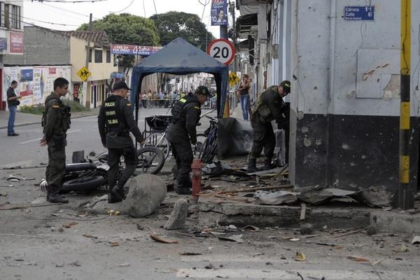Policías revisan los daños causados por una moto bomba el jueves en el departamento del Valle del Cauca.   AFP.