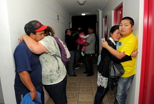 Los habitantes de un edificio de apartamentos se abrazan en uno de los pasillos del inmueble a la espera de evacuar la ciudad de Iquique, Chile, una de las más golpeadas por el terremoto de 8,2 grados Richter de este martes.