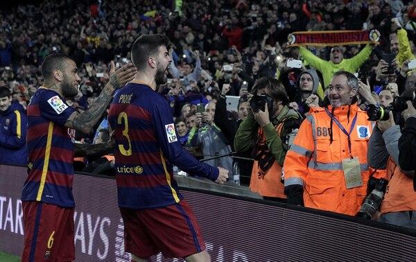 El defensa del FC Barcelona Gerard Piqué junto a su compañero, Daniel Alves, celebra el gol marcado ante el Real Madrid.