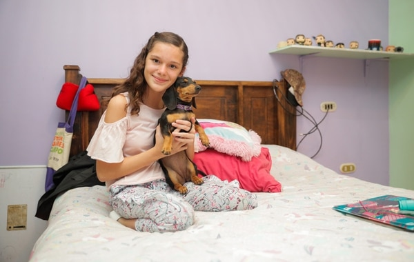 Sentarse en su cama sola, sin necesidad de ayuda, era algo que hasta hace relativamente poco no podía hacer Ana Belén. Aquí, en su habitación con una de sus mascotas más queridas, Brisa. Foto Jeffrey Zamora