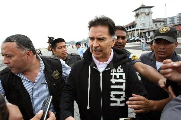 El expresidente Alfonso Portillo es conducido al avión que lo esperaba en el aeropuerto internacional La Aurora, en Ciudad de Guatemala, para trasladarlo –el 24 de mayo del 2013– a Estados Unidos.   AFP