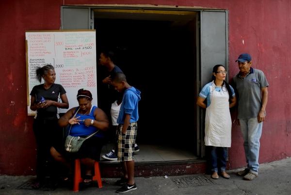 Trabajadores y vecinos permanecían fuera de un comercio en Caracas, este martes 26 de marzo del 2019, mientras la ciudad seguía sin electricidad.