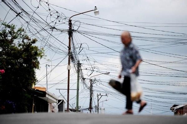 La cantidad de cables que tienen y la mala ubicación, obligó a la CNFL a lanzar un plan de reacomodo en 21 cantones de la GAM.   ARCHIVO.