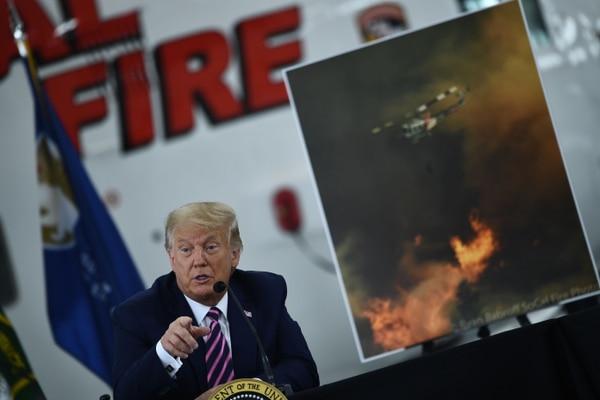 El presidente de Estados Unidos, Donald Trump, habla en una sesión informativa sobre los incendios forestales con funcionarios locales y bomberos en el aeropuerto de Sacramento McClellan, durante visita a California, el 14 de setiembre del 2020. Foto: AFP