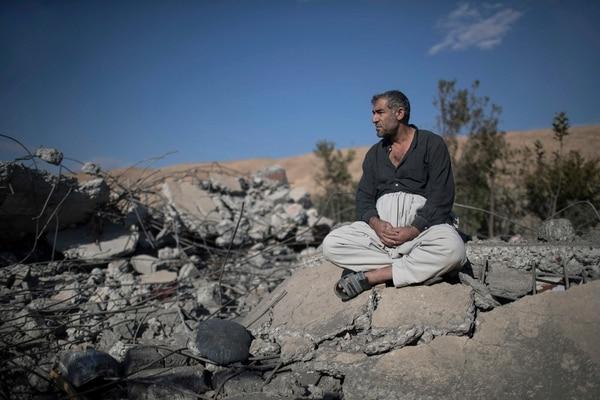Yusuf Mohammed Yusuf sentado sobre los escombros de lo que fue la causa de un hermano, destruida por un bombardeo aéreo en Faziliya, al norte de Mosul.