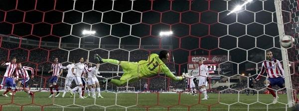 Keylor Navas intenta detener el remate que hizo el uruguayo José María Giménez, pero su lance no sirvió para evitar la segunda anotación del Atlético en el Vicente Calderón.   EFE