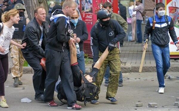 Manifestantes prorrusos cargan con un compañero herido durante los enfrentamientos con los partidarios de Ucrania Unida, en la ciudad de Odessa Ucrania este viernes.