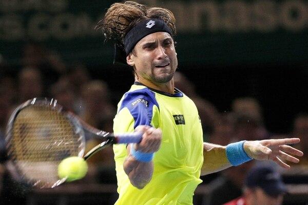 El español David Ferrer remata esta pelota hacia el campo de su compatriota Rafael Nadal, a quien venció este sábado 6-3 y 7-5 en el Masters de París.