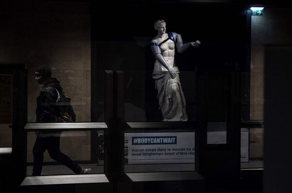 Un hombre camina junto a una réplica de la Venus de Milo con brazos protésicos simbólicamente unidos durante una acción dirigida por Handicap International para crear conciencia sobre los miles de amputados en todo el mundo que necesitan una prótesis, en la estación de metro Louvre-Rivoli en París, e 6 de marzo de 2018. Foto: AFP
