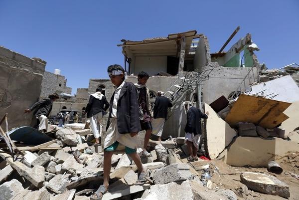 Yemeníes caminaban entre los escombros de viviendas destruidas en Saná por un bombardeo de la coalición que encabeza Arabia Saudí. Ocurrió el 29 de marzo del 2015.