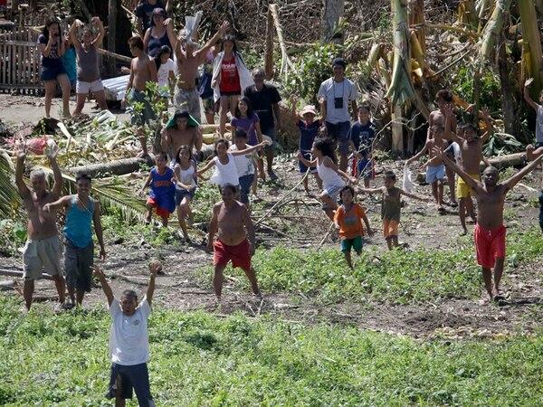 Personas aisladas en La Paz, isla de Leyte, aguardaban ayer el descenso de un helicóptero de la Fuerza Aérea filipina que les traía víveres.   AP