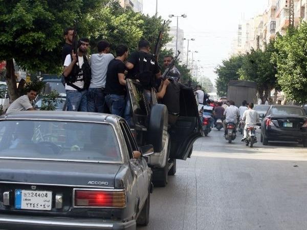 Hombres armados transitaron hoy por las calles de Trípoli para protestar por la muerte de Wisam al Hasan.   AFP
