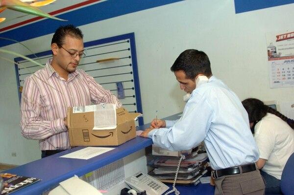 Las empresas de casilleros y logística prometen descuentos y más rápidez en las entregas. En la foto Jorge Varela recoge un paquete de compras y es atendido por Jos Leitón, de Jet Box.
