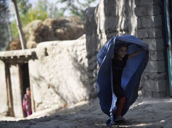 Una niña afgana jugó con su burka la semana pasada en el valle de Payan Shahr en la provincia de Badakhshan. La prenda es considerada un símbolo de represión hacia las mujeres. | AFP.