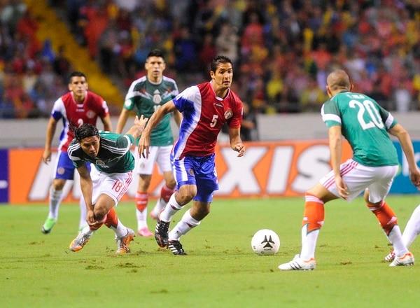 El volante costarricense Celso Borges condude el balón ante la marca de Jorge Torres Nilo de México.