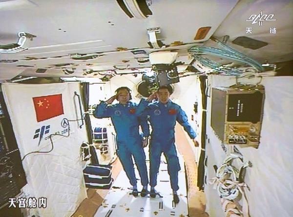 Jing Haipeng (izq) Chen Dong saludan tras su ingreso al laboratorio Tiangong-2 ('Palacio Celeste-2').
