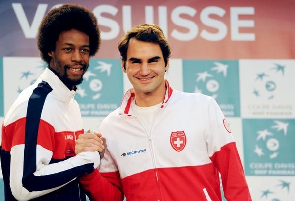 Roger Federer estrecha su mano con el francés Gael Monfils (izq.) con quien jugará el viernes en la Copa Davis.