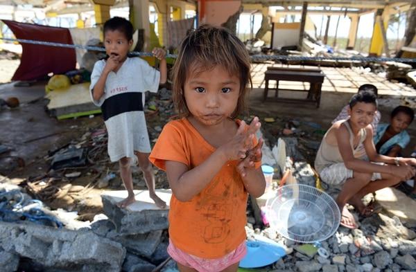 Niños afectados por el tifón deambulaban ayer por una escuela destruida en el poblado de Hernani. | AFP.