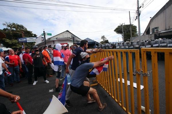Desde que llegaron a Presidencia, en Zapote, los manifestantes intentaron retirar las vallas de seguridad a la fuerza. Fotografía: Alonso Tenorio.