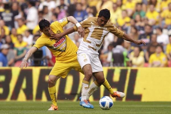 El jugador de América Rubens Sambueza (izq.) disputa el balón con Javier Cortés (der.) de Pumas.