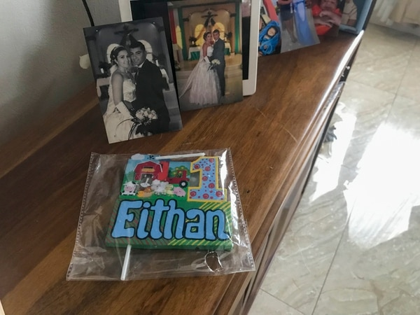 La candela para el queque de su primer año espera por Eithan en la repisa llena de fotografías de la familia Brenes Alvarado. Foto: Ángela Ávalos
