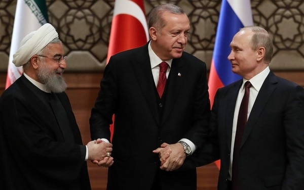 El presidente de Irán, Hassan Rohaní, el presidente de Turquía, Recep Tayip Erdogan, y el presidente de Rusia, Vladimir Putin, se dan la mano después de una conferencia de prensa conjunta como parte de una cumbre tripartita sobre Siria, en Ankara, el 4 de abril de 2018. AFP