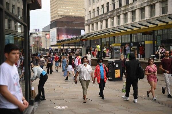 Clientes caminaban a lo largo de una calle en la ciudad de Mánchester, Inglaterra, este viernes 31 de julio del 2020. AFP