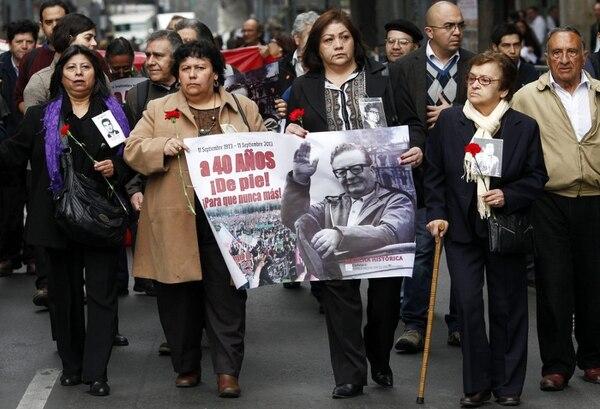 La presidenta de la Agrupación de Familiares de Detenidos Desaparecidos, Lorena Pizarro (segunda, derecha) marcha hoy junto con un grupo de personas hacia el monumento al expresidente chileno Salvador Allende.