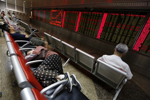 Algunos inversinistas duermen frente a las pantallas que muestran los indicadores bursátiles en Pekín. | EFE