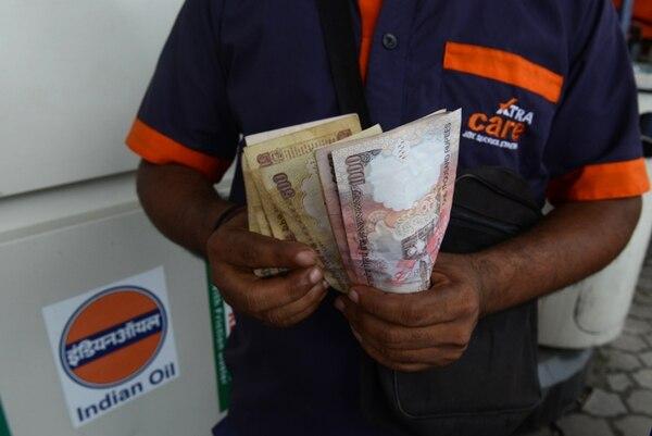 Un hombre en una calle de Nueva Deli cuenta rupias, la moneda nacional hoy fuertemente devaluada a causa de la crisis económica en India.   AFP.