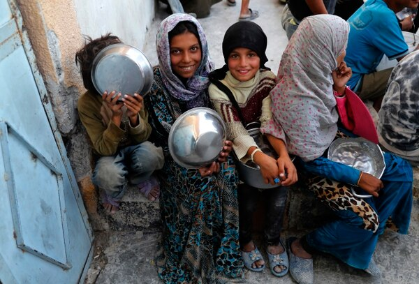Niñas desplazadas sirias que huyeron de la ciudad de Raqa sostienen recipientes mientras esperan recibir alimentos en la entrada de la cocina principal de un campo de refugiados en Ain Isa.
